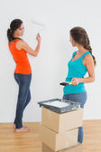 Female friends with paint brushes in a new house — Stock Photo