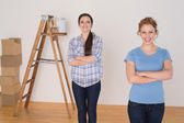 Friends standing with arms crossed in a new house — Stock Photo