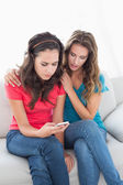 Upset female friends reading text message at home — Foto Stock