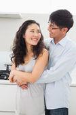 Uomo donna che abbraccia da dietro in cucina — Foto Stock