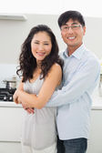 Young man embracing woman from behind in kitchen — Stock Photo