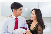 Couple with gift box in the kitchen at home — Stock Photo