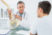 Doctor explaining spine to a patient in office — Stock Photo