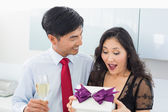 Shocked woman opening a gift box by man with champagne — Stock Photo