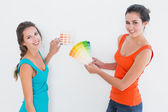 Female friends choosing color for painting a room — Stock Photo