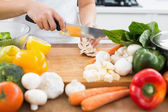 Mid section of a woman chopping vegetables in kitchen — Stock Photo