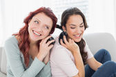 Friends listening music through headphones together at home — Stock Photo