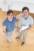 Male therapist gesturing thumbs up with disabled patient — Stock Photo