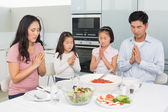 Family of four saying grace before meal in kitchen — Foto Stock