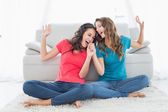 Cheerful female friends singing in the living room — Stock Photo