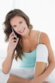 Smiling woman in tank top using mobile phone in bed — Stock Photo