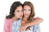 Young female embracing her friend from behind — Stock Photo