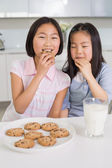 Two smiling girls enjoying cookies and milk in kitchen — Stock Photo
