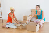 Friends unwrapping boxes in a new house — Stock Photo