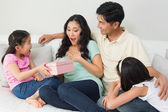 Family presenting surprised mother with a gift box in living room — Foto de Stock