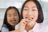 Little girl feeding her elder sister a cookies in kitchen — Photo