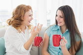Friends with coffee cups conversing at home — Stock Photo