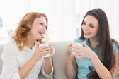 Female friends with coffee enjoying a conversation at home — Stock Photo