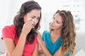 Woman consoling a crying female friend at home — Stock Photo