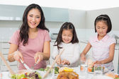Woman with two little girls having food in kitchen — Stock Photo