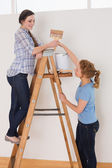 Friends with paintbrush and can on ladder in a new house — Stockfoto