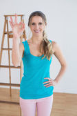 Woman gesturing okay sign against ladder in a new house — Stockfoto