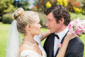 Bride and groom embracing and smiling at each other — Foto Stock