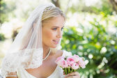 Happy bride in a veil holding her bouquet — Stock Photo