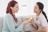 Happy female friends toasting wine glasses at home — Stock Photo