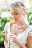 Smiling blonde bride in pearl necklace smelling rose — Stock Photo
