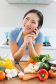 Mujer mediante teléfono móvil delante de verduras en la cocina — Foto de Stock