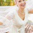 Pretty happy blonde bride holding her veil out smiling at camera — Stock Photo #37833223
