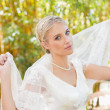 Pretty content blonde bride holding her veil out smiling at camera — Stock Photo #37834275