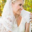 Beautiful blonde bride holding her veil and smiling — Stock Photo #37830127