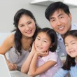Portrait of a family of four with laptop in kitchen — Stock Photo