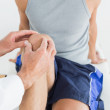 Close-up of a man getting his knee examined — Stock Photo #37830803