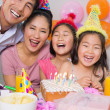 Stock Photo: Cheerful family with cake and gifts at a birthday party