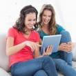 Female friends using digital tablet in the living room — Stock Photo #37830935