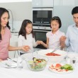 Family of four saying grace before meal in kitchen — Stock Photo #37831017
