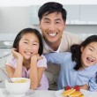 Smiling man with happy daughters having breakfast in kitchen — Stock Photo