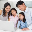 Happy family of four using laptop in kitchen — Stock Photo #37831619