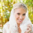 Beautiful blonde bride holding her veil smiling at camera — Stock Photo #37831765