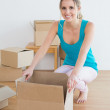 Happy young woman unwrapping boxes in new house — Stock Photo #37832173