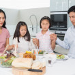 Family of four saying grace before meal in kitchen — Stock Photo #37832767