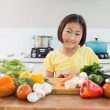 Cute young girl with raw vegetables at the kitchen counter — Stock Photo