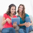 Smiling female friends using digital tablet in the living room — Stock Photo