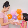Woman giving gift box to a little girl at a birthday party — Stock Photo