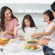 Family of four enjoying healthy meal in kitchen — Stock Photo