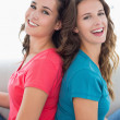 Female friends sitting back to back in living room — Stock Photo #37833617