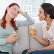 Female friends with wine glasses chatting on sofa at home — Stock Photo